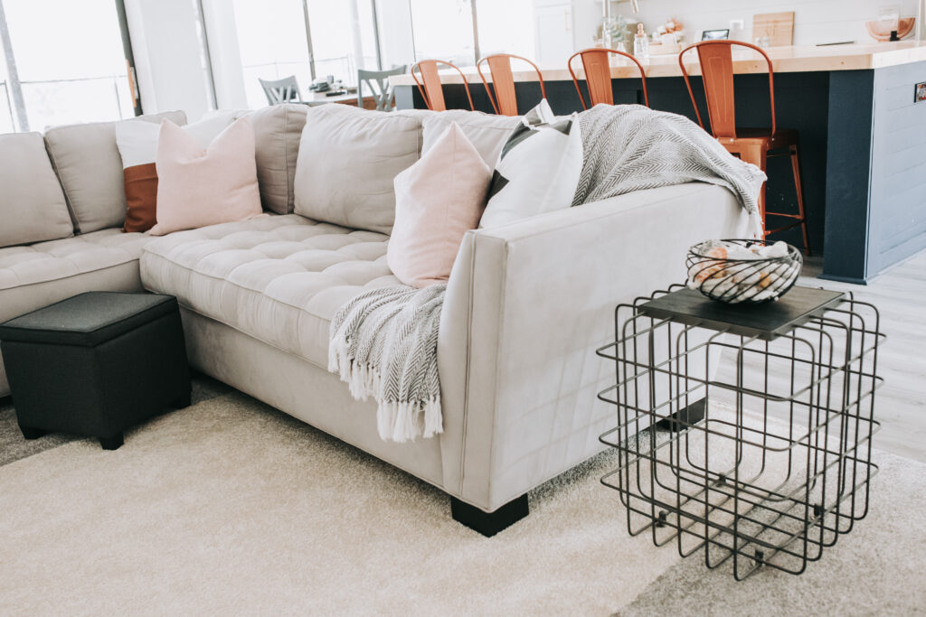 light gray sectional with blush pillows and Woven Nook throw pillow covers, home decor finds, summer home decor trends