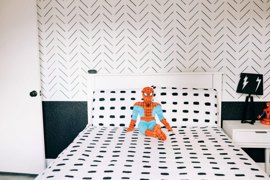 boy in Spiderman costume against a sharpie wall decor