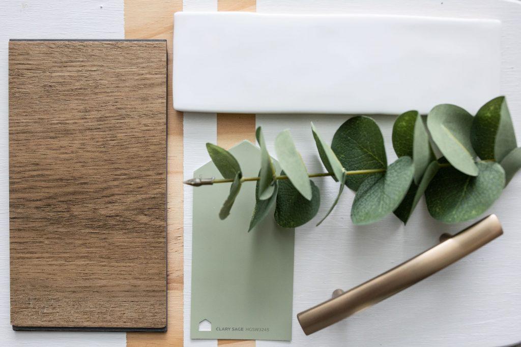 modern kitchen renovation with white tile, sage green island, brass hardware pulls and warm honey oak vinyl plank flooring